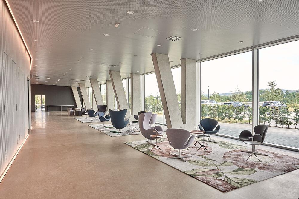 Eingangshalle mit Sesseln von Fritz Hansen und floralen Teppichen in gedeckten Farben