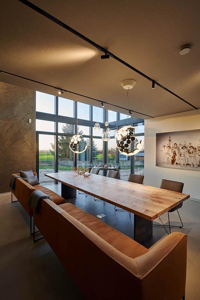 Raumaustattung Esszimmer mit großen Ledersofas und Holztisch, sowie Hängelampen