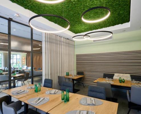 Restaurant Ausstattung mit Moosdecke und runden Deckenleuchten