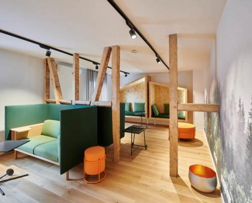 raumideen Gemütlicher Rückzugsraum mit Holzelementen, Waldtapete und grünen und orangenen Polsterlementen