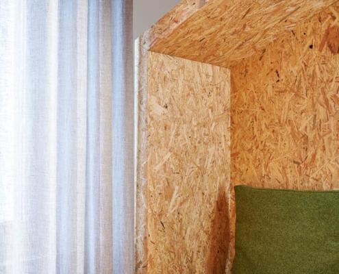 Detailaufnahme Rückzugsraum aus Presspanplatten mit grünen Polstern
