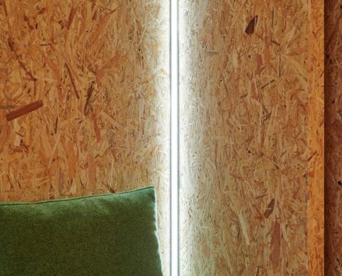 Sperrholzwandverkleidung mit grünen Polstern und Lichtinstallation