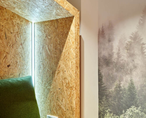 Sitzecke mit Pressspanwänden und grünen Polstern neben Waldtapete