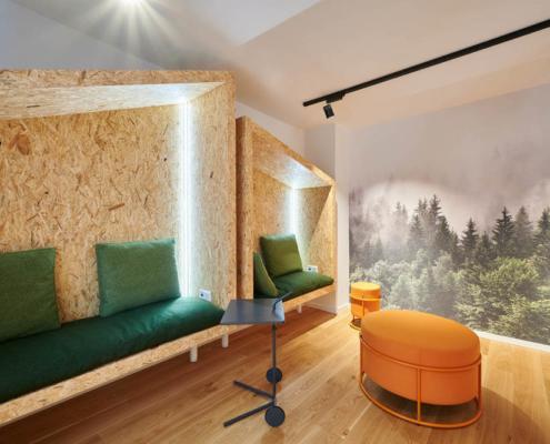 gemütlicher Rückzugsraum mit Waldtapete und grünen und orangenen Details