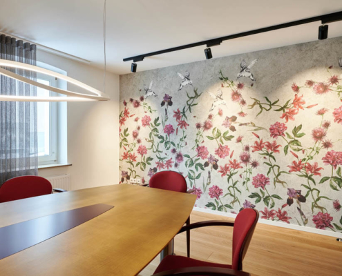 Besprechungsraum mit floraler Wandtapete und roten Elementen