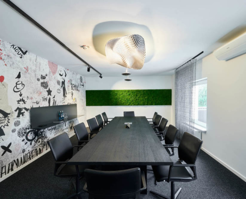 Konferenzraum mit Mooswand und bunter Wandtapete