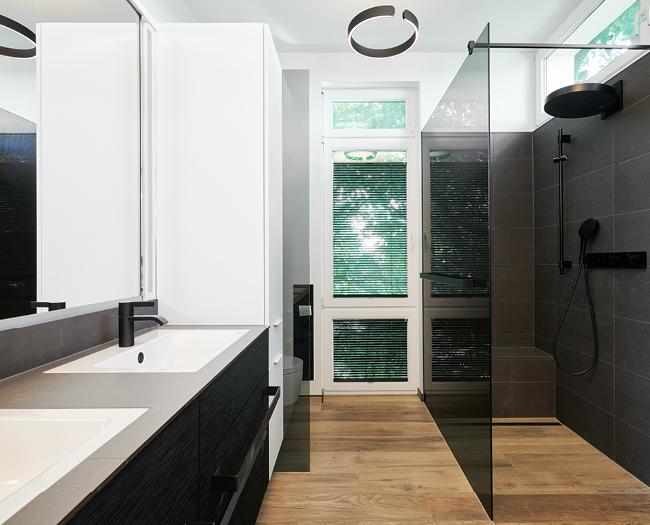 Abbildung des Badumbaus mit Blick auf die neue Dusche, den maßangefertigten Waschtisch und der Beleuchtung von Occhio